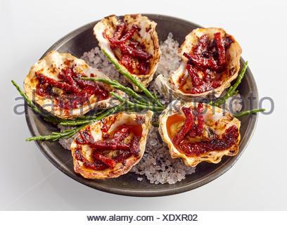 Close Up Still Life sur une assiette d'Huîtres Kilpatrick préparé avec du bacon et du fromage et servi avec du sel garnir sur fond blanc Banque D'Images
