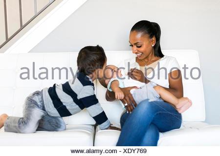 Mère avec deux fils (2-5 mois, 2-3) sur canapé