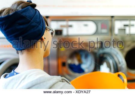 Vue arrière de jeune femme dans une laverie Banque D'Images