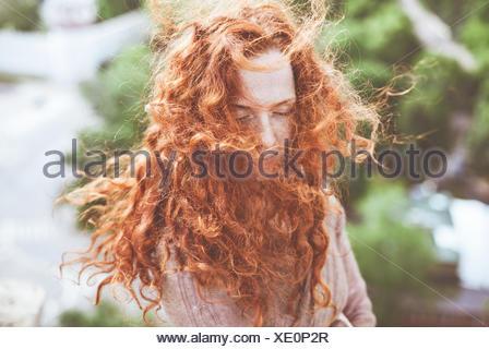 Portrait de jeune femme aux longs cheveux roux bouclés, Banque D'Images