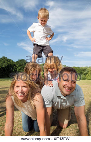 Famille avec trois enfants jouant dans un parc. Banque D'Images