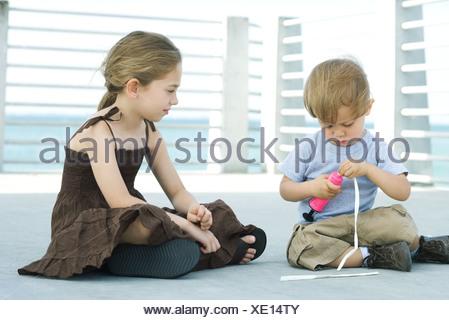 Petit garçon assis sur le sol du gonflage ballon avec pompe à air, sœur aînée de regarder Banque D'Images