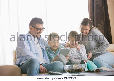 Happy Family using tablet PC in living room Banque D'Images