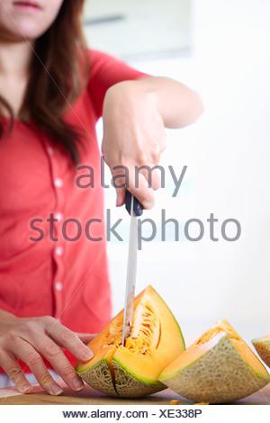 Jeune femme dans la cuisine trancheuse melon Banque D'Images