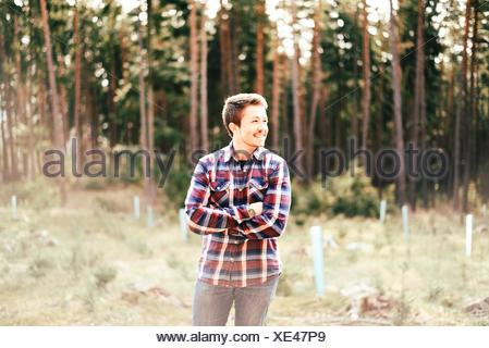 Happy Man Standing With Arms Crossed In Forest Banque D'Images