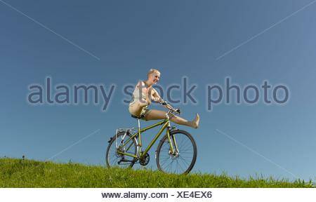 Une femme sur un vélo de descente en roue libre en été Banque D'Images