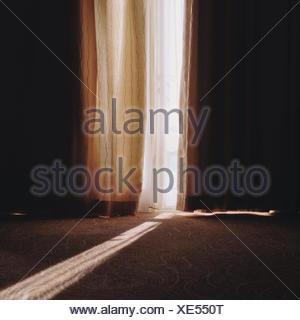 Sunbeam qui brillait à travers les rideaux en écart Banque D'Images