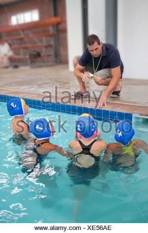 Lycéenne quatre joueurs de water-polo à l'écoute au bord de l'enseignant Banque D'Images