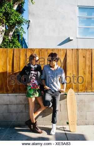Jeune couple à l'extérieur, skateboard leaning on wall en regard de l'homme