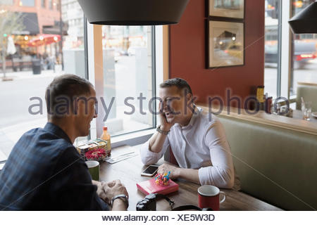 Male gay couple relaxing at diner booth Banque D'Images