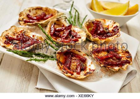 Close Up Still Life Voir des huîtres, assiette de Kilpatrick préparé avec du bacon et du fromage et servi sur table en bois peint avec serviette et quartiers de citron Banque D'Images