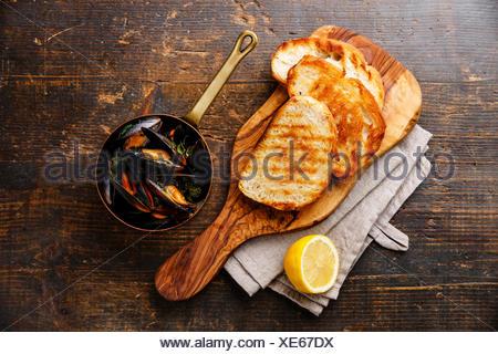 Moules dans marmite en cuivre, toasts de pain et de citron sur fond de bois