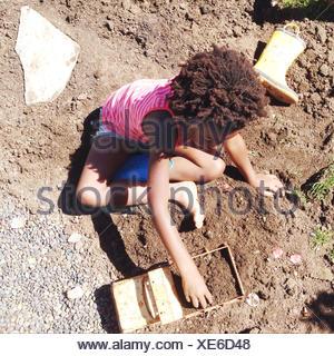 Fille assise sur le sol en jouant avec un camion jouet Banque D'Images