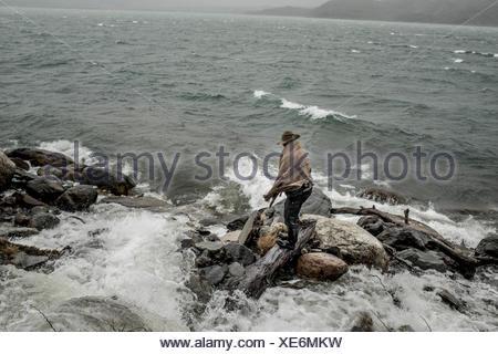 Un bagualero, cowboy qui capture l'élevage sauvages, se dresse sur des rochers au bord de l'eau. Banque D'Images