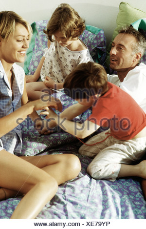 Family playing together in bed Banque D'Images