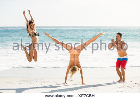Belle amis excités de sauter sur la plage Banque D'Images