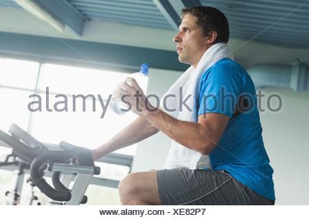 Homme fatigué avec de l'eau bouteille working out at spinning class Banque D'Images