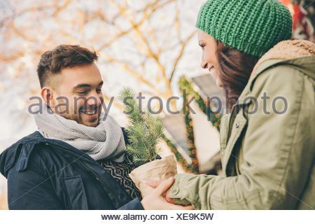 L'homme de la réception d'un petit arbre dans un pot d'une femme sur le marché de Noël Banque D'Images