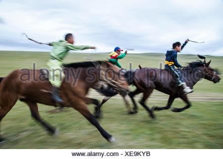 Les courses de chevaux sont à l'âge de cinq ans avec les coureurs de moins de 13 ans lorsqu'ils prendront leur retraite. La plupart des riders wear capes satin aux couleurs vives et des costumes d'être reconnu de loin. La plupart des rendez-bareback, bien que quelques tour sur light racing de selles. Plusieurs seulement porter des bas pour réduire le poids des bottes encombrants et presque tous ont un dashur une récolte d'exhorter leurs chevaux. Ils se font concurrence pour 20 kilomètres bareback course de chevaux. Dans Bunkhan Lantern Festival annuel, la Mongolie. Banque D'Images