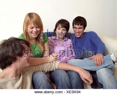 Groupe d'amis adolescents ayant une conférence sur le canapé Banque D'Images