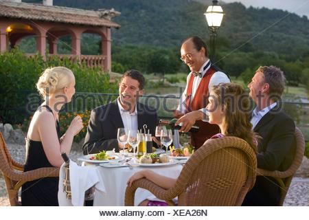Waiter pouring wine bien habillés pour des couples à table sur balcon restaurant Banque D'Images