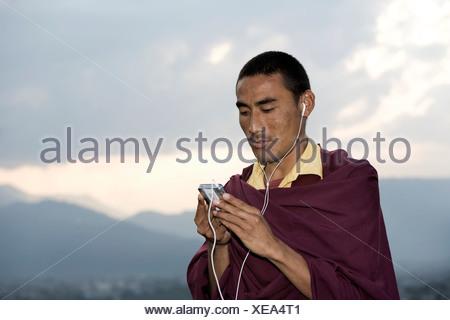 Pokhara, Népal, moine à l'écoute de i-Pod Banque D'Images