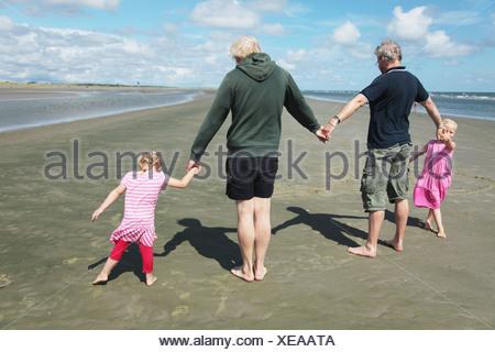 Vue arrière des parents et leurs filles (4-7) holding hands on beach Banque D'Images