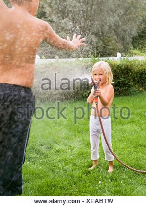 Pulvériser de l'eau sur Garçon Fille Banque D'Images