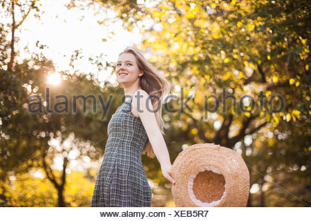 Teenage girl holding chapeau running in park