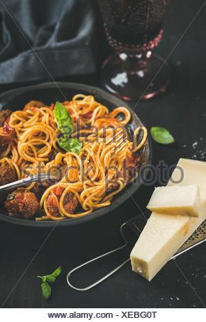 Dîner de pâtes italiennes. Spaghetti avec meatballas, basilic et parmesan dans le noir et la plaque en verre de vin rouge sur fond noir, selective focus. Banque D'Images