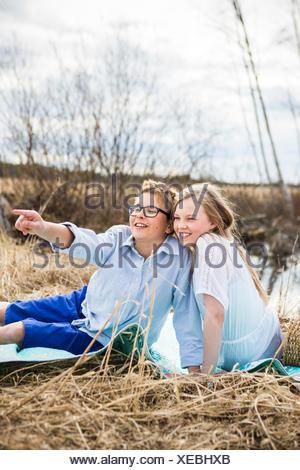 La Finlande, l'Aanekoski, Amerique, Girl (12-13) and boy (12-13) assis sur une couverture à l'extérieur et à l'écart Banque D'Images