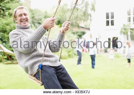 Man se balançant dans la cour avec la famille Banque D'Images