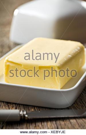 Cube de beurre à l'aide d'un couteau sur fond de bois Banque D'Images
