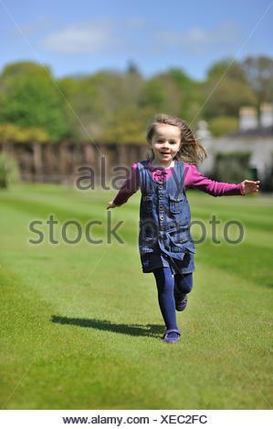 Little girl (4-5) s'exécutant sur l'herbe verte Banque D'Images