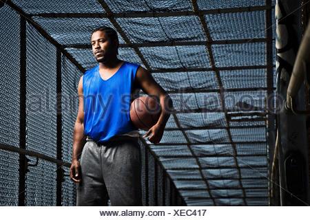 Un jeune homme pose avec un terrain de basket-ball sur un pont. Banque D'Images
