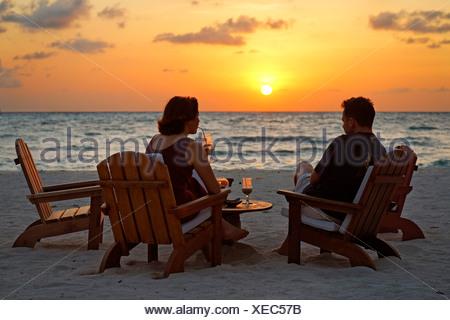 Couple assis sur des chaises à la plage avec des long drinks devant un coucher du soleil doré, Rihiveli, Island, Maldives, South Male Ato Banque D'Images