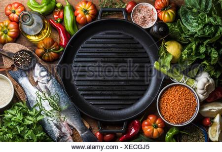 Ingrédients pour cuisiner un dîner sain. Le bar avec des poissons crus crus les légumes, les céréales, le riz, les herbes et épices et gril noir Banque D'Images