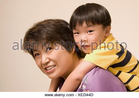 Close-up of a young woman giving piggyback ride à son petit-fils Banque D'Images