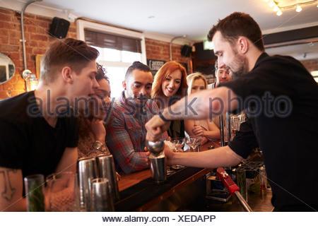 Barman Cocktail donnant des leçons à vos amis en Bar Banque D'Images