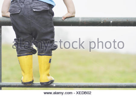 Boy standing on clôture métallique Banque D'Images
