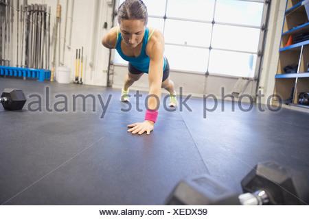 Femme déterminée faisant un bras push-ups in gym Banque D'Images