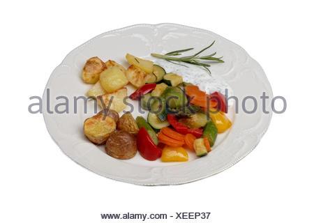 Plaque isolée avec légumes et pommes de terre au four Banque D'Images