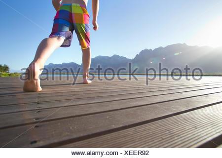Boy running à sauter dans un lac d'une jetée Banque D'Images