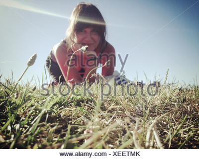 Portrait of Woman with Hand On Chin assis sur l'herbe Banque D'Images