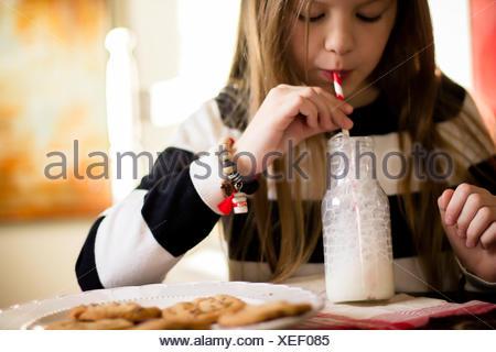 Girl blowing bubbles dans la bouteille de lait et une assiette de cookies Banque D'Images