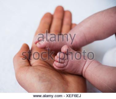 Père tenant les pieds d'un bébé nouveau-né dans ses mains Banque D'Images