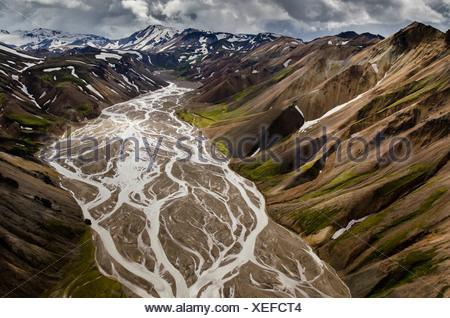 Vue aérienne, Joekulgilkvísl rivière tressée, montagnes de rhyolite partiellement recouvert de neige, Landmannalaugar Banque D'Images