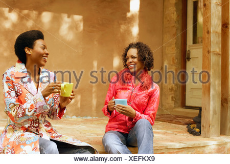 Jeune femme et une mature woman holding coffee cups and smiling Banque D'Images