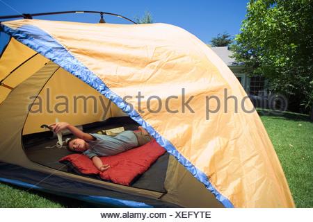 Boy 810 couché sur un sac de couchage rouge orange à l'intérieur de tente sur jardin pelouse Playing with toy aero avion vue arrière Banque D'Images