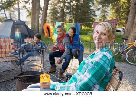 Family relaxing together autour de feu de camp Banque D'Images